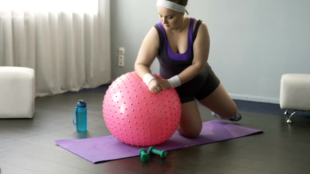 överviktig dam försöker träna, roliga försök att ligga på stora fitness boll - ofullkomlighet bildbanksvideor och videomaterial från bakom kulisserna