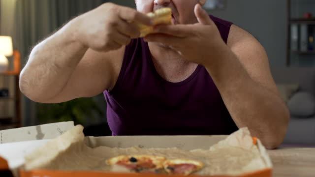 stockvideo's en b-roll-footage met mannelijke eten pizza snel overgewicht bij nacht, verslaving aan ongezonde voeding - dikke pizza close up