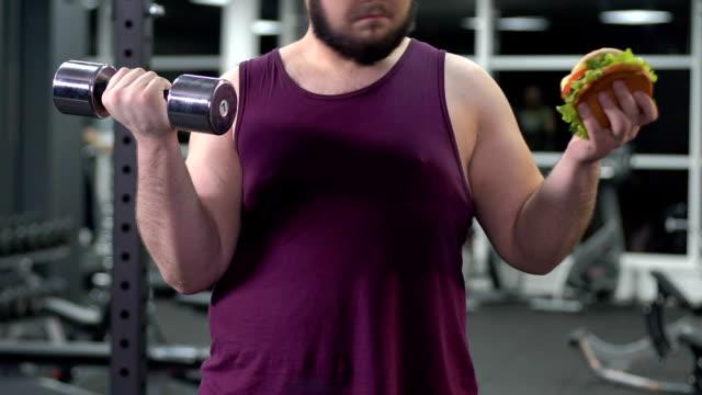 stockvideo's en b-roll-footage met overgewicht man met hamburger en halter in handen voor het kiezen van gezond leven - ongezond leven