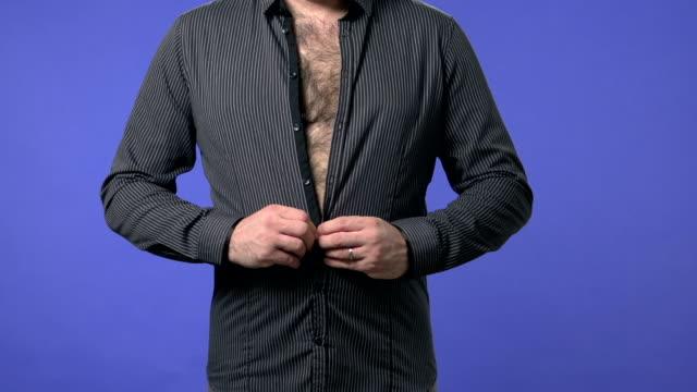 Overweight man buttoning a shirt video