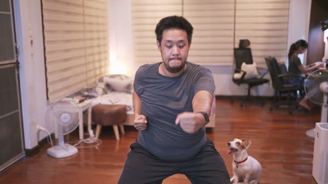 överviktig man gör cardio stansning hiit motion online training session hemma i covid-19 corona virus situation - hemmaträning bildbanksvideor och videomaterial från bakom kulisserna