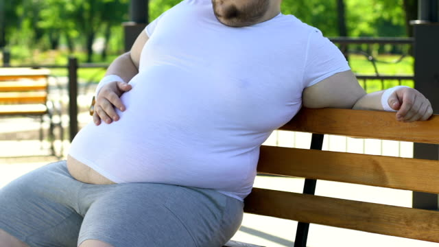 overweight man feeling back ache after exhausting training, obesity consequences - sovrappeso video stock e b–roll