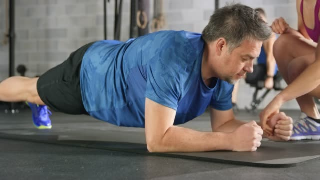 Overweight man holding plank position in fitness under female trainer supervision