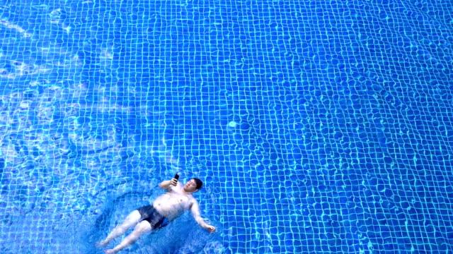 vídeos de stock, filmes e b-roll de homem obeso deitado na água enquanto estiver usando o telefone - flutuando na água