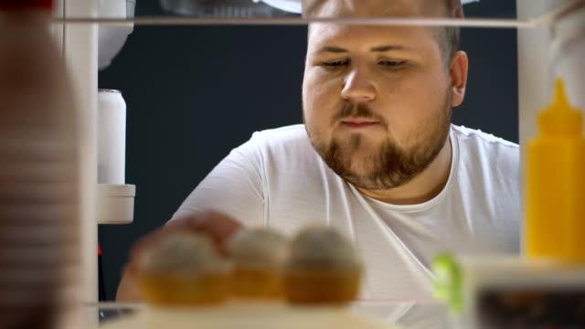stockvideo's en b-roll-footage met overgewicht man openen koelkast en heerlijke crème taart eten 's nachts, dieet - ongezond leven