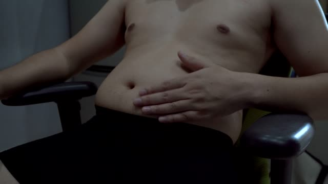 stockvideo's en b-roll-footage met overgewicht man zittend op een stoel, met de nadruk op uw eigen vorm - ongezond leven