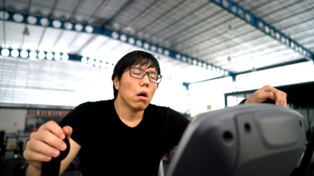 Overweight Nerd Man exhausted from running on treadmill at gym