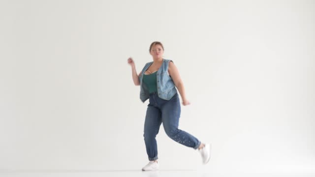overweight woman dancing in studio - pesante video stock e b–roll