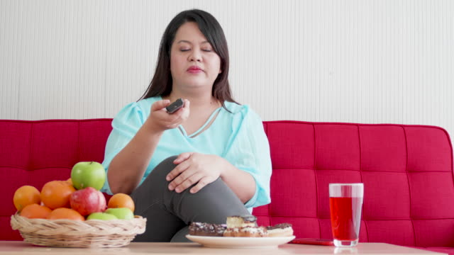 Overweight Woman enjoy eating donut and using laptop