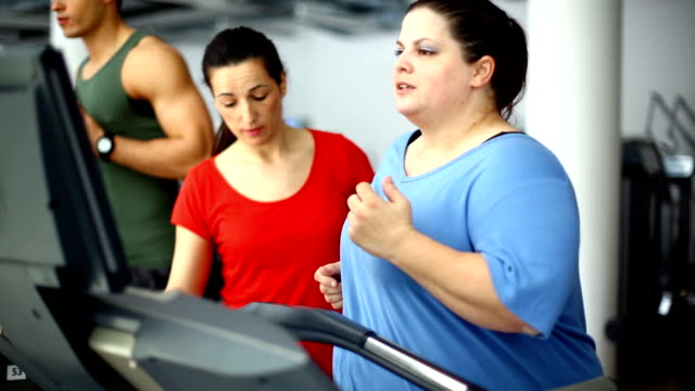 Overweight woman exercising on a treadmill. video