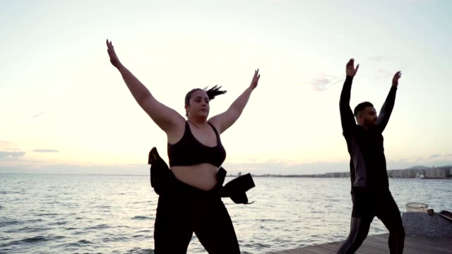 Overweight woman exercising with trainer Overweight woman is doing cardio exercise with her personal trainer by the sea. plus size model stock videos & royalty-free footage