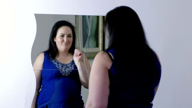 overweight woman is checking her look at the mirror: happy overweight woman video