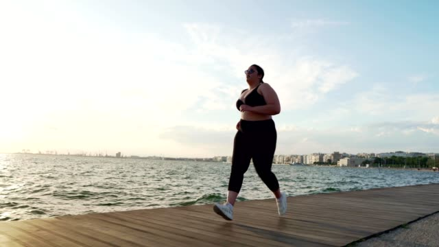 overweight woman jogging - body positive video stock e b–roll
