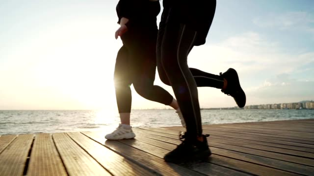 Overweight woman jogging with trainer Low-section of overweight woman jogging by the sea with her personal trainer. large build stock videos & royalty-free footage