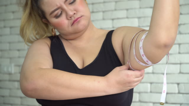 Overweight woman  measuring her arm