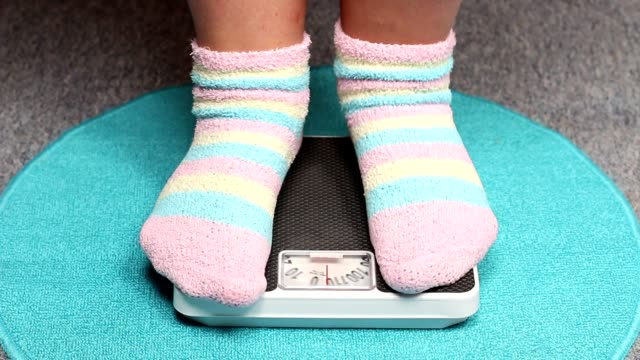 Overweight woman on a weight scale. Overweight woman on a weight scale. Slimming and dieting theme. plus size model stock videos & royalty-free footage