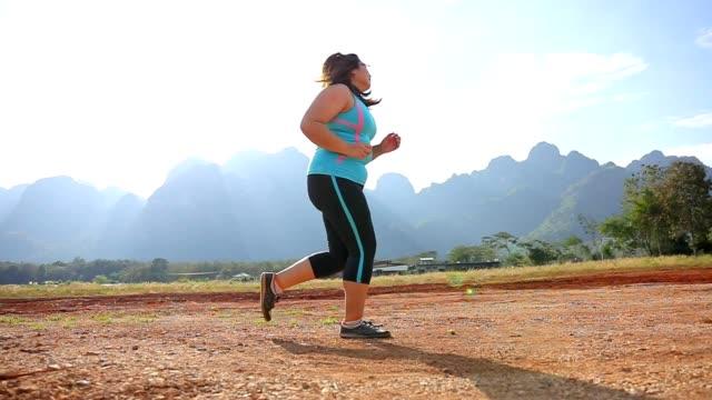 朝のスローモーションで公園で走っている太りすぎの女性 - 肥満点の映像素材/bロール