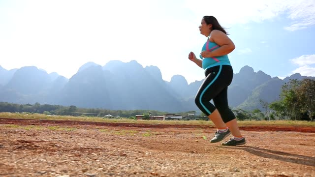 overweight woman running in park in the morning - sovrappeso video stock e b–roll