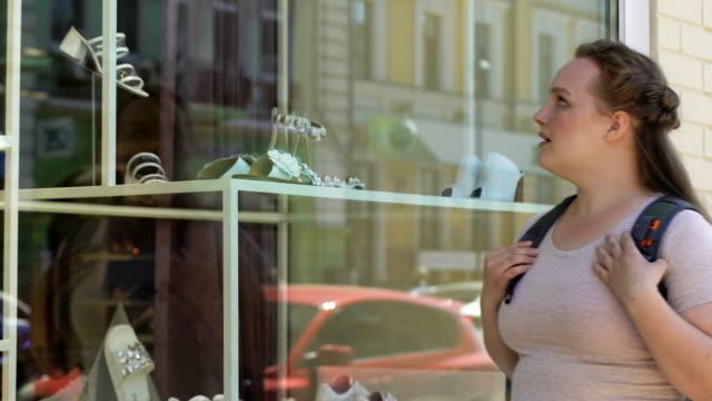 übergewichtige frau leider teure schuhe in luxus schaufenster betrachten, träumen - schaufenster stock-videos und b-roll-filmmaterial
