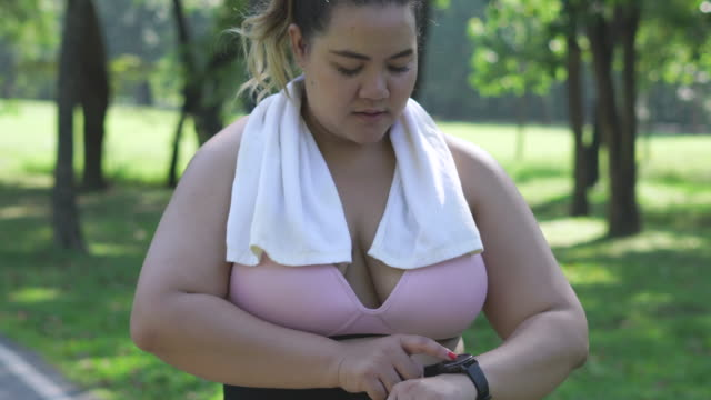 donna in sovrappeso che imposta l'orologio intelligente prima di correre - body positive video stock e b–roll
