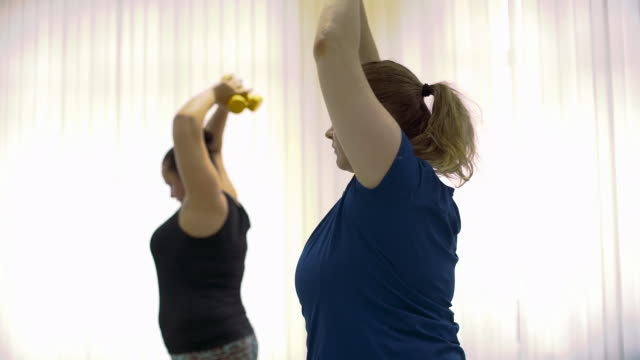 Overweight Women Doing Exercises to Lose Fat Plump Women Working Out with Dumbbells in a Gym. Overweight Women Doing Exercises to Lose Fat. Healthcare, Sport, Fitness, Weight Losing, Active Lifestyle Concept plus size model stock videos & royalty-free footage