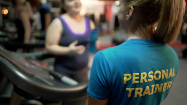 Overweight young woman asking personal training for advice on exercises in gym video