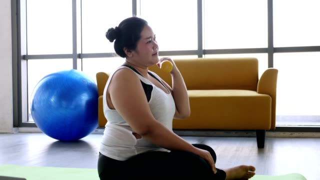 Overweight young woman exercising to lose weight at home video