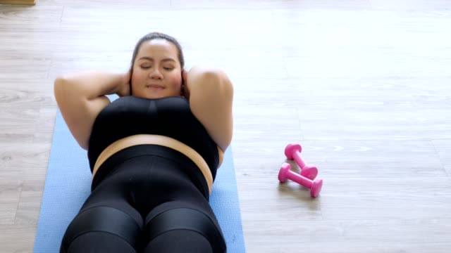 vídeos de stock e filmes b-roll de overweight young woman in sportswear exercising to lose weight at home - roupa desportiva