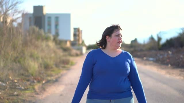 stockvideo's en b-roll-footage met overgewicht jonge vrouw lopen op de straat - ongezond leven