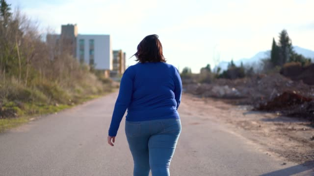 overweight young woman walking on the street - тяжёлый стоковые видео и кадры b-roll