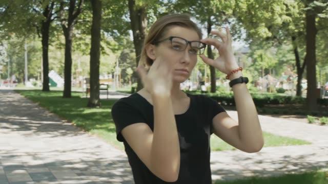 vidéos et rushes de femme caucasien accablé dans des lunettes transpirant et souffrant le coup de chaleur marchant dans un stationnement une journée chaude d'été - canicule