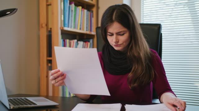 vídeos y material grabado en eventos de stock de mujer abrumada con documentos y portátil en casa - trabajo de oficina