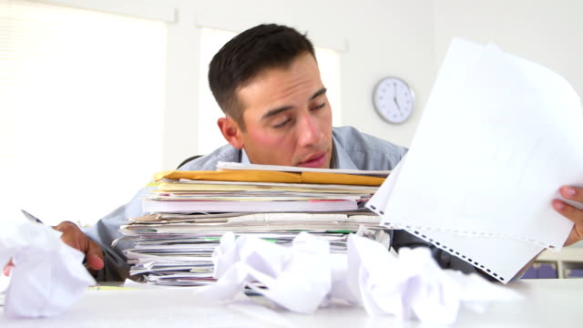 Overworked business man with large stack of papers video