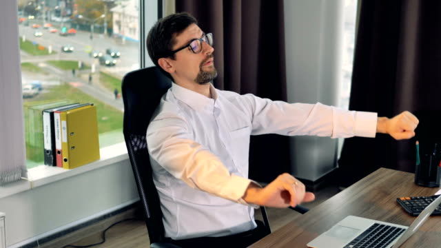 Overworked businessman stretches his arms during work. A businessman takes a break from a laptop to stretch arms and lean in his chair. stretching stock videos & royalty-free footage