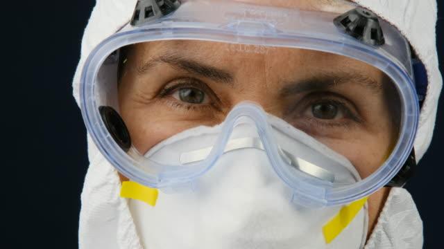 lavoratrice che tiene in mano una siringa con un vaccino covid-19 - occhiali protettivi video stock e b–roll