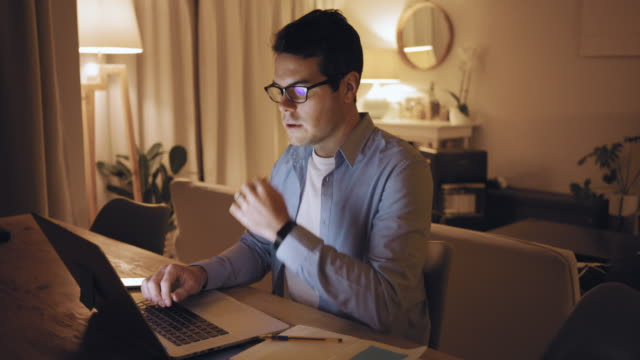 Overworked man massage his nose bridge feeling stress while using laptop