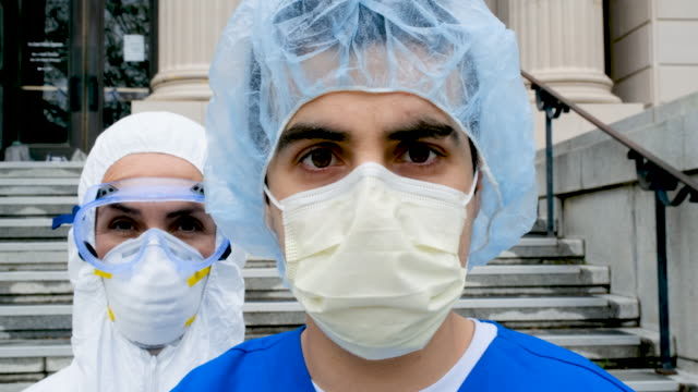 overworked, tired serious health care workers looking at the camera - infermiera personale medico video stock e b–roll