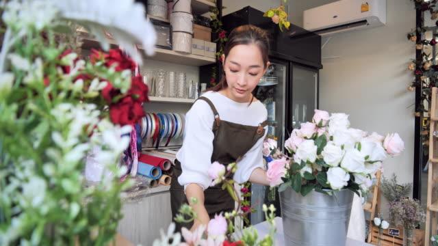 di proprietà fiorista fiore asiatico donna all'interno del negozio per prepararsi per la vendita, una donna giapponese con fioristi professionisti, negozi di fiori in città, concetto di piccola impresa. - bouquet video stock e b–roll