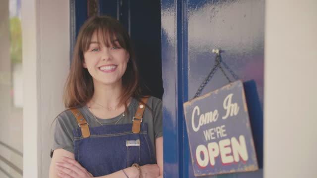 ägaren står armar korsas av öppna tecken på delikatesser dörr - liten bildbanksvideor och videomaterial från bakom kulisserna