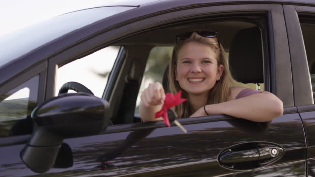 Owning my first car Teenage girl jingles new car keys with a bow on them out the driver window and waves while smiling and laughing with excitement. car key stock videos & royalty-free footage