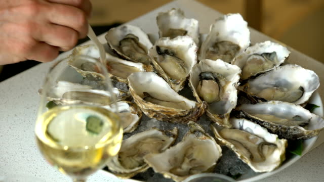 Oysters and glass of champagne in a restaurant. video
