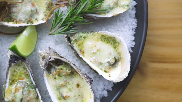 Oysters baked with cheese, lime and herbs on plate. Presentation menu seafood restaurant. Mediterranean cuisine. Serving seafood composition top view. Healthy nutrition concept