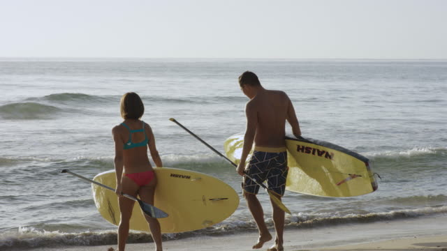 Pacific islander man and woman entering water with SUP boards video