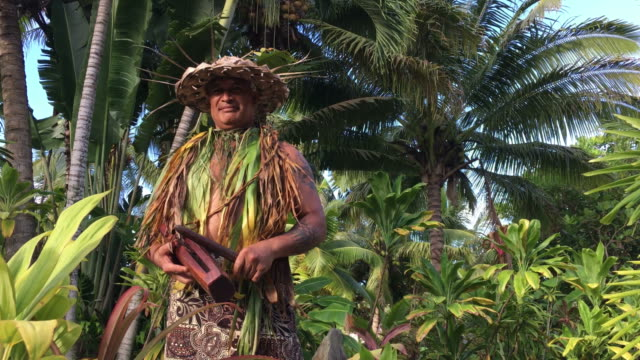 Pacific Islander man plays on a small Pate wooden stick drum Pacific Islander man plays on a small Pate wooden stick drum instrument in Rarotonga, Cook Islands. pacific islands stock videos & royalty-free footage