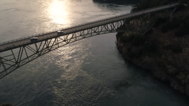 Pacific Northwest Aerial of Cars Crossing Ocean Bridge to Puget Sound Island with Golden Hour Lens Flare video