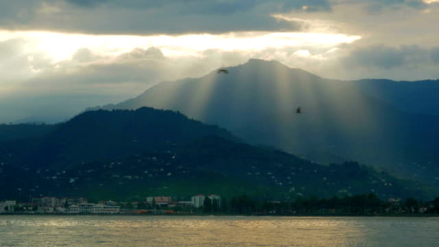 Pacific Ocean and the mountains behind. From the clouds make their way rays of the sun. After the rain video