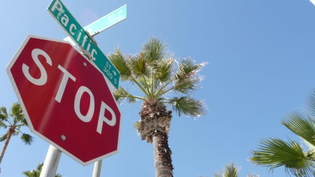 Pacific street road sign on crossroad, route 101 tourist destination, California, USA. Lettering on intersection signpost, symbol of summertime travel and vacations.Signboard in city near Los Angeles