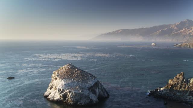 vídeos de stock e filmes b-roll de pacific swirling around cliffs and islands near gamboa point, big sur - drone shot - big sur