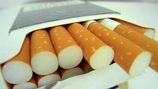 un pacchetto di sigarette su sfondo bianco - sigaretta video stock e b–roll