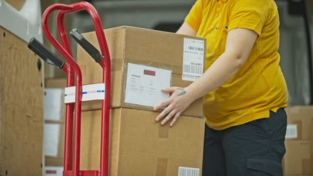 Package delivery worker stacking packages onto the cart